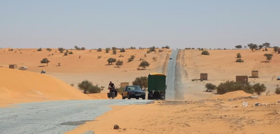 La route nationale, jonchée de trous à certains endroits, au danger fréquent des routes africaines